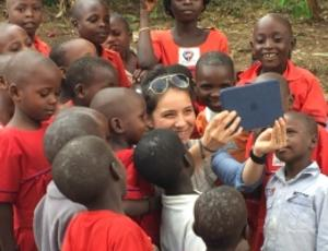 Military engineer takes picture of herself with group of Ugandan kids.